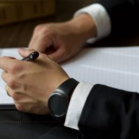 person-on-black-suit-jacket-writing-on-white-paper-940829